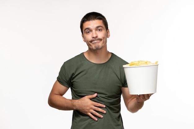 Giovane maschio di vista frontale in maglietta verde che tiene le patatine fritte sulla persona sola del cinema di film dello scrittorio bianco