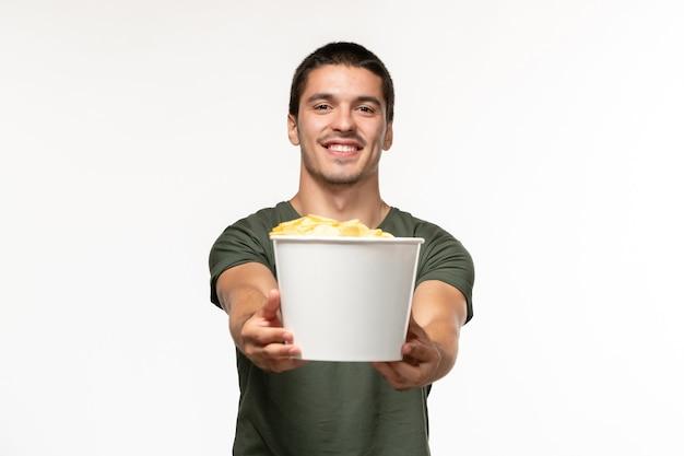 Giovane maschio di vista frontale in maglietta verde che tiene le patatine fritte sulla persona solitaria del cinema di film del film della parete bianca