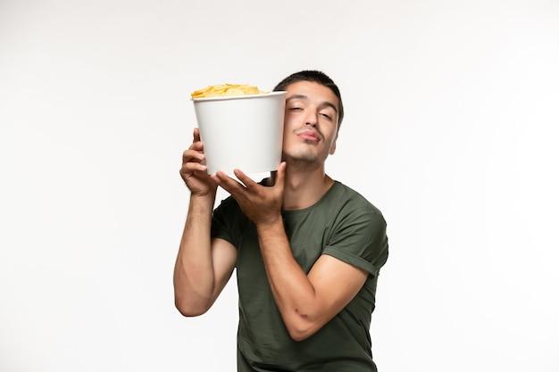 Giovane maschio di vista frontale in maglietta verde che tiene le patatine fritte sulla parete bianca persona solitaria film cinema