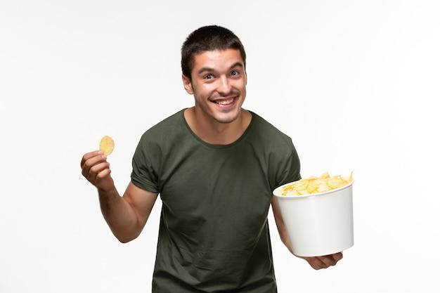 Giovane maschio di vista frontale in maglietta verde con patatine fritte e mangiare sul cinema di film film solitario persona scrivania bianca