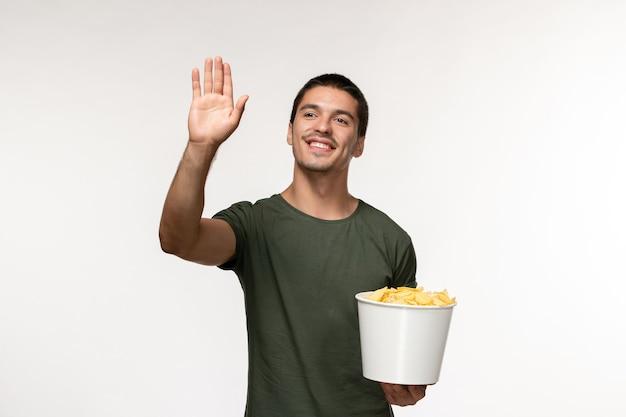 Giovane maschio di vista frontale in maglietta verde con le patatine fritte e saluto qualcuno sul cinema di film solitario maschio della persona del film della parete bianca
