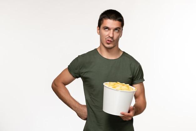 Vista frontale giovane maschio in maglietta verde con patatine fritte sul muro bianco chiaro film persona maschio film solitario cinema