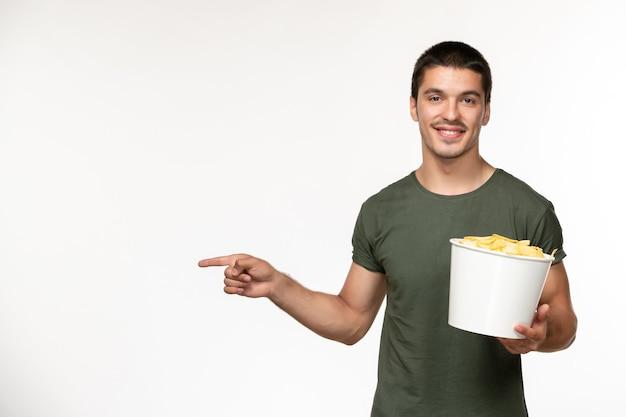 Giovane maschio di vista frontale in maglietta verde con le patatine fritte e sorriso sul cinema di film solitario della persona del film della parete bianca