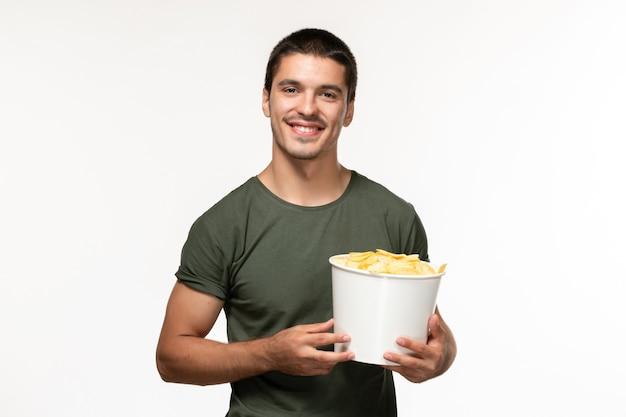 Giovane maschio di vista frontale in maglietta verde con le patatine fritte che sorride sul cinema solitario di film della persona del film della parete bianca