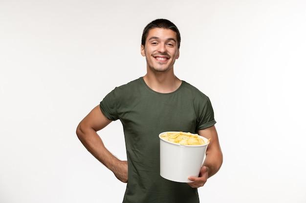 Giovane maschio di vista frontale in maglietta verde con le patatine fritte che sorride sul cinema di film solitario maschio della persona del film della parete bianca