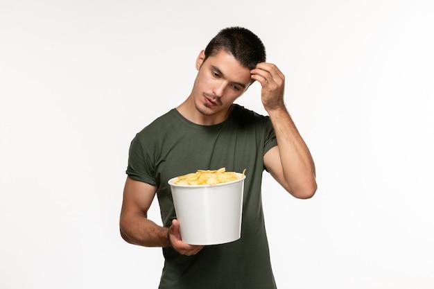 Giovane maschio di vista frontale in maglietta verde con le patatine fritte che pensa sul cinema di film solitario maschio della persona del film della parete bianca