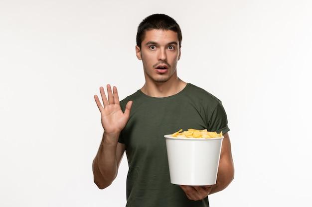 Giovane maschio di vista frontale in maglietta verde con le patatine fritte che guardano film sul cinema solitario di film della persona del film della scrivania bianca