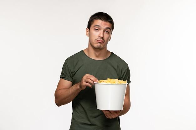 Giovane maschio di vista frontale in maglietta verde con le patatine fritte che guardano film sul cinema di film solitario maschio della persona del film della parete bianca