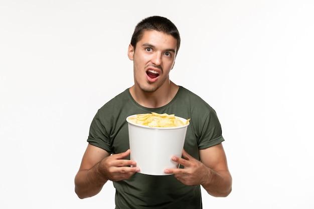 Giovane maschio di vista frontale in maglietta verde con le patatine fritte sul cinema solitario di film della persona del film della parete bianca
