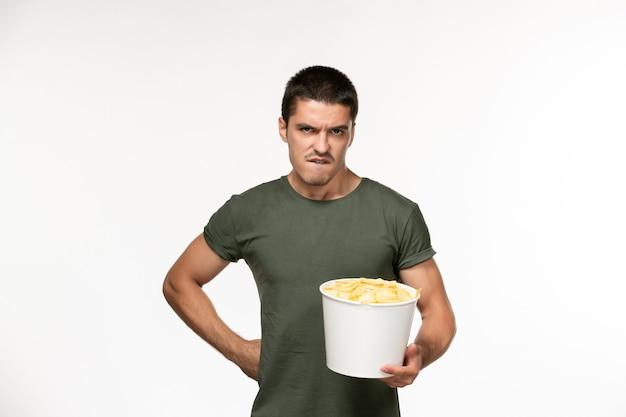 Giovane maschio di vista frontale in maglietta verde con patatine fritte sul cinema di film solitario maschio della persona del film della parete bianca