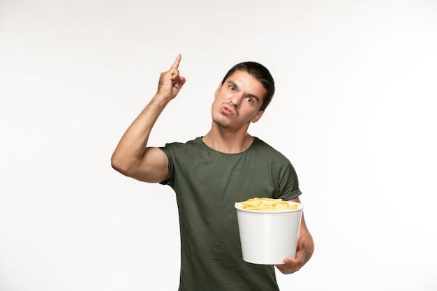 Giovane maschio di vista frontale in maglietta verde con le patatine fritte sul cinema di film solitario della persona della parete bianca