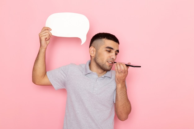 Front view young male in grey shirt holding white sign and talking on phone on pink