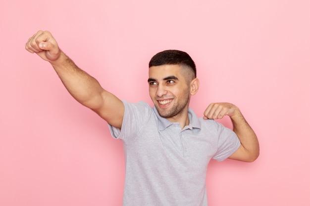 Giovane maschio di vista frontale in camicia grigia che posa nel segno del supereroe sul rosa