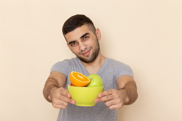 Front view young male in grey t-shirt and blue jeans holding plate with fruits smiling on beige