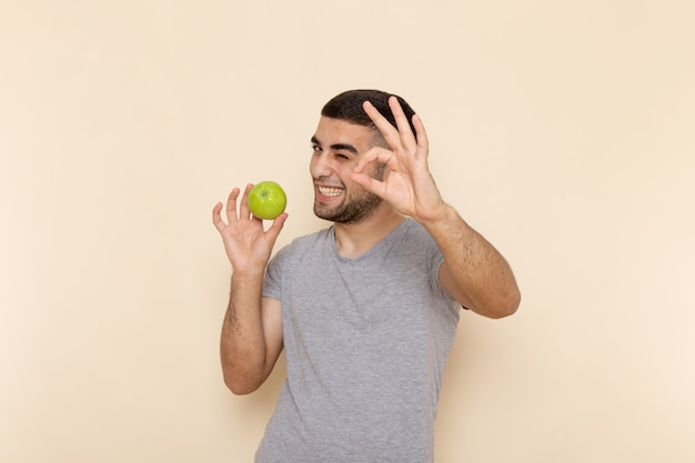 Front view young male in grey t-shirt and blue jeans smiling and holding green apple on beige