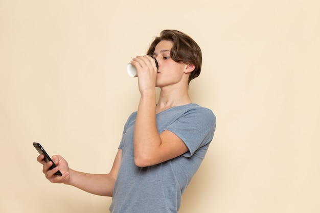 A front view young male in grey t-shirt drinking coffee and using a phone