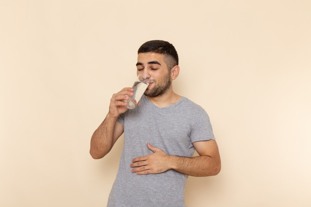 Front view young male in grey t-shirt drinking glass of water on beige