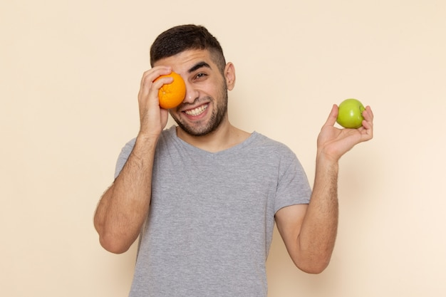 Front view young male in grey t-shirt holding apple and orange desk