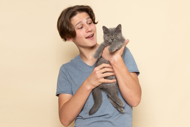 A front view young male in grey t-shirt holding cute grey kitten
