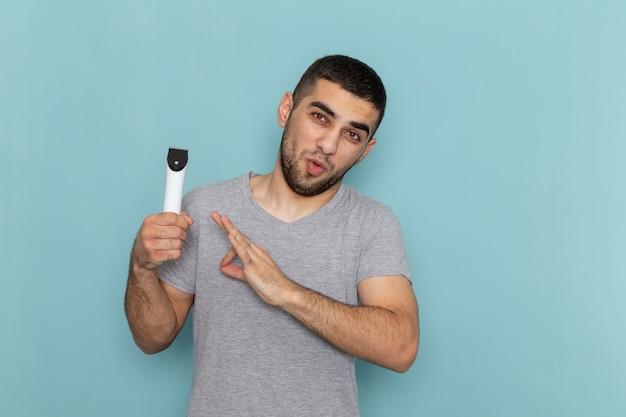 Giovane maschio di vista frontale in maglietta grigia che tiene il rasoio elettrico sulla schiuma maschio dei capelli della barba di rasatura dello scrittorio blu
