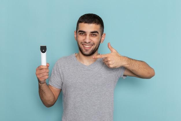 Giovane maschio di vista frontale in maglietta grigia che tiene il rasoio elettrico sulla schiuma dei capelli maschii della barba da barba blu