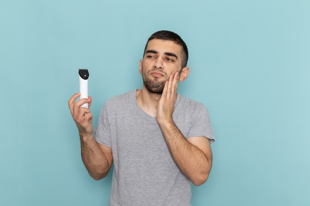 Front view young male in grey t-shirt holding electric razor on ice-blue male shaving beard hair foam
