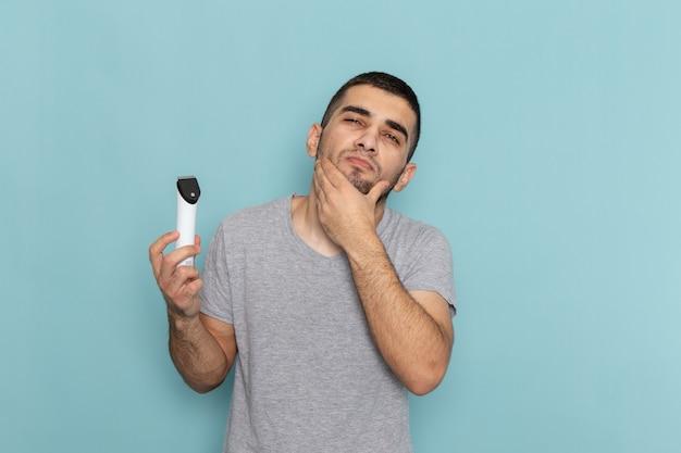 Giovane maschio di vista frontale in maglietta grigia che tiene il rasoio elettrico sulla schiuma dei capelli della barba da barba maschio blu ghiaccio