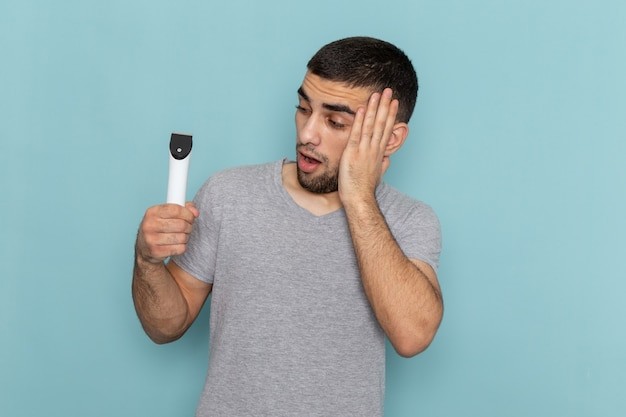 Front view young male in grey t-shirt holding electric razor with surprised expression on the blue