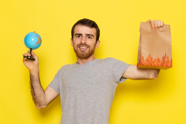 A front view young male in grey t-shirt holding food package and little globe on the yellow wall man color model emotion clothes