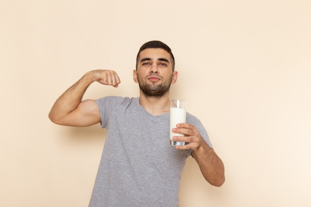 Front view young male in grey t-shirt holding glass of milk on beige