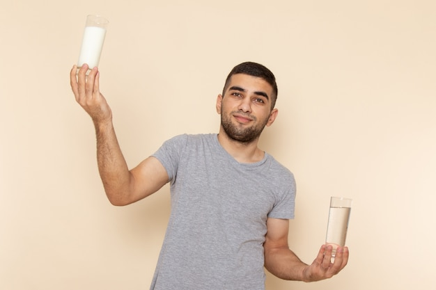 Front view young male in grey t-shirt holding glass of water and milk on beige