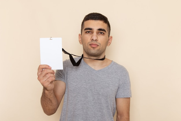 Front view young male in grey t-shirt holding identity card