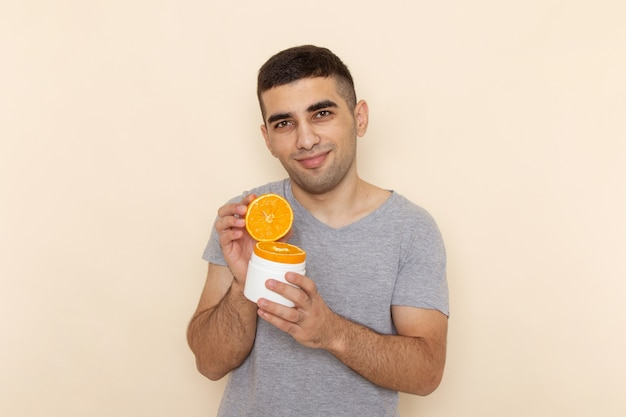 Front view young male in grey t-shirt holding orange slices with slight smile on beige