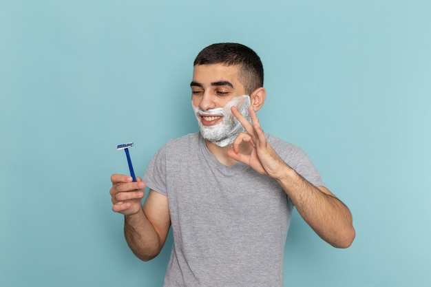 Front view young male in grey t-shirt holding razor on iced-blue beard foam shaving male