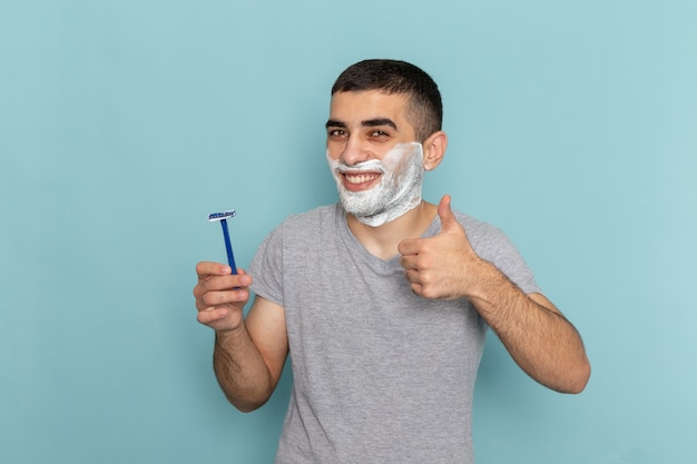 Front view young male in grey t-shirt holding razor and smiling on ice-blue beard foam shaving male