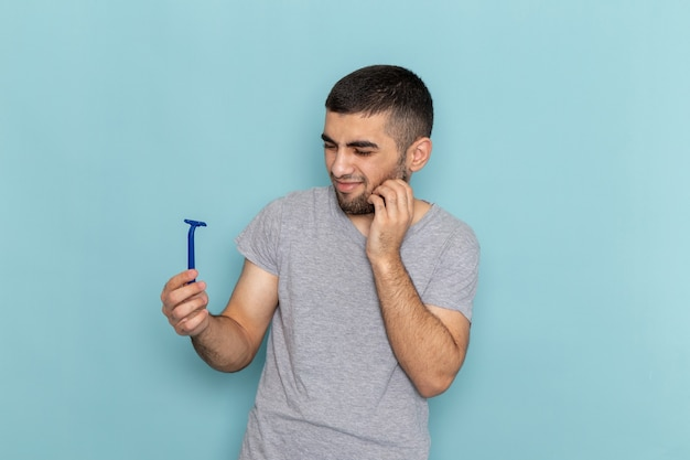 Front view young male in grey t-shirt holding razor with displeased expression on the blue