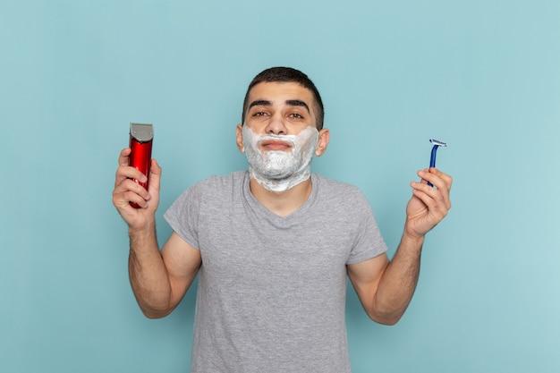 Giovane maschio di vista frontale in maglietta grigia che tiene rasoio semplice ed elettrico sul maschio di rasatura della schiuma della barba blu ghiaccio
