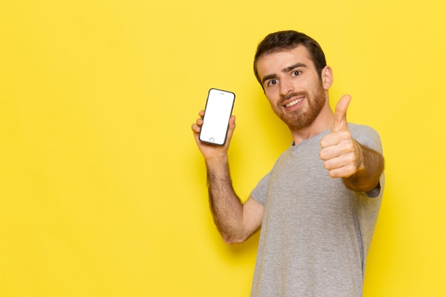 A front view young male in grey t-shirt holding smartphone with smile on the yellow wall man color model