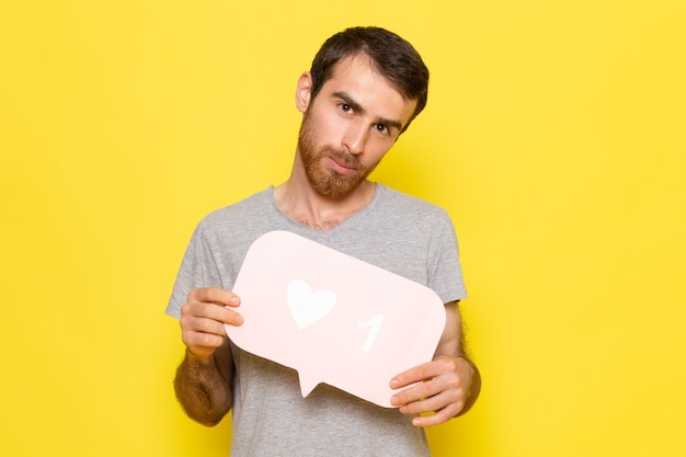 A front view young male in grey t-shirt holding white sign on the yellow wall man expression emotion color