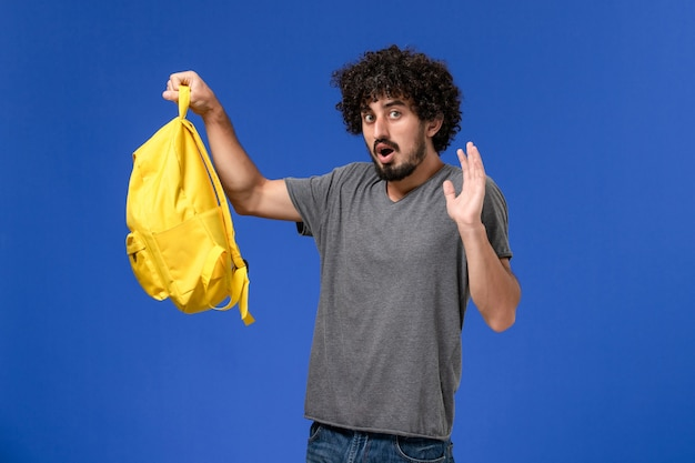 Front view of young male in grey t-shirt holding yellow backpack on the blue wall