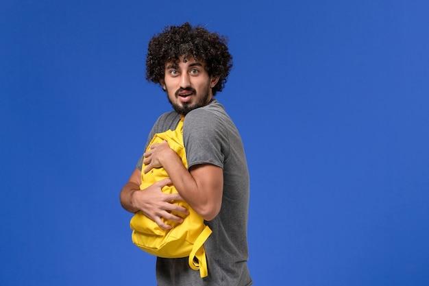 Vista frontale del giovane maschio in maglietta grigia che tiene lo zaino giallo sulla parete blu
