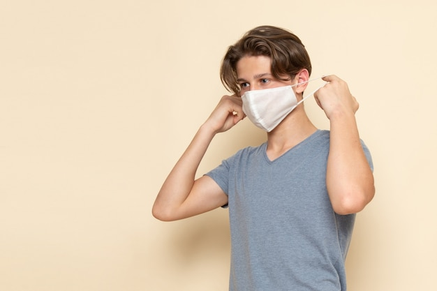 Un giovane maschio di vista frontale in maglietta grigia che porta una maschera