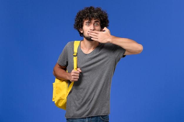 Vista frontale del giovane maschio in maglietta grigia che porta zaino giallo chiudendo la sua bocca sulla parete blu