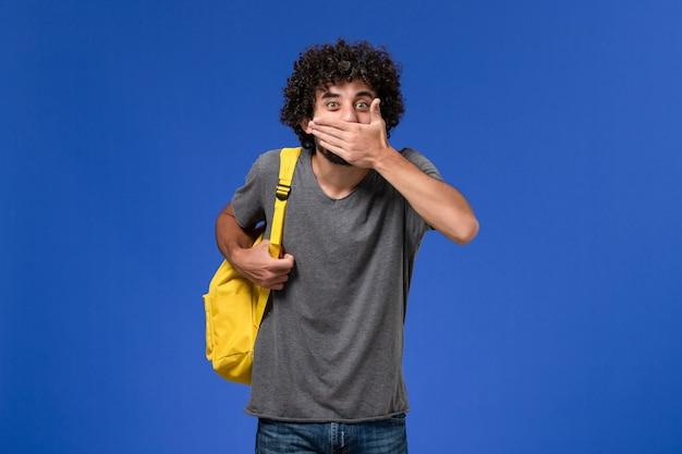 Vista frontale del giovane maschio in maglietta grigia che indossa lo zaino giallo che copre la bocca sulla parete blu