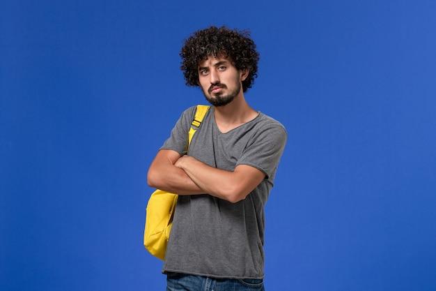 Vista frontale del giovane maschio in maglietta grigia che porta zaino giallo che pensa profondamente sulla parete blu