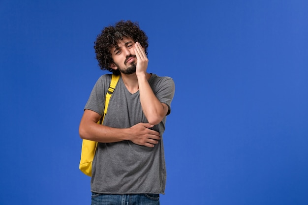 Front view of young male in grey t-shirt wearing yellow backpack having toothache on the blue wall