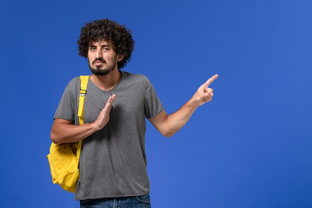 Front view of young male in grey t-shirt wearing yellow backpack just posing on blue wall