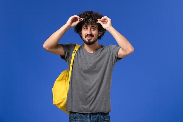 Vista frontale del giovane maschio in maglietta grigia che porta zaino giallo che sorride appena sulla parete blu