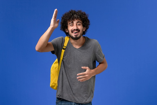 Front view of young male in grey t-shirt wearing yellow backpack laughing on the blue wall