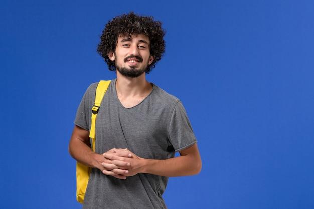 Vista frontale del giovane maschio in maglietta grigia che porta zaino giallo sorridente sulla parete blu